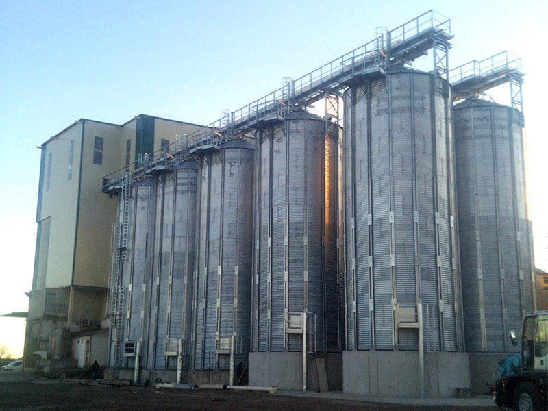 Flat bottom silos for raw material in a feed mill